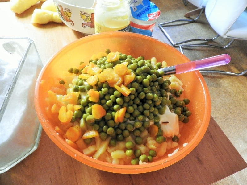Salad Olivier: Add carrots and peas, salt and pepper